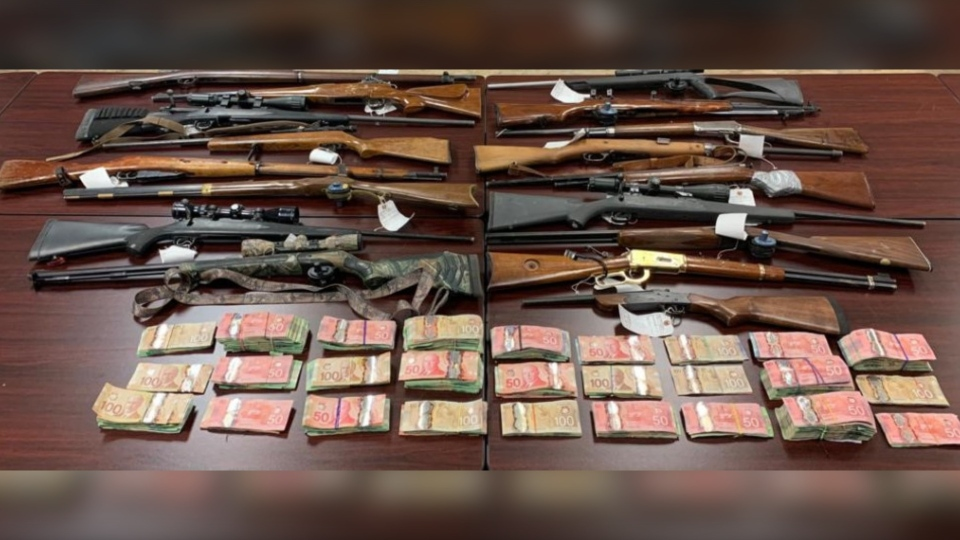 The RCMP included this photo, showing 17 guns and a sum of cash. (Photo: New Brunswick RCMP)