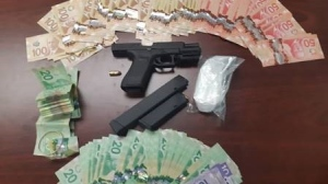 A loaded Glock semi-automatic hand gun, 98 grams of suspected cocaine and $10,000 in cash was seized from a traffic violation on Friday, February 27, 2021 (Source: Sarnia Police, Community Patrol Branch - D Platoon)