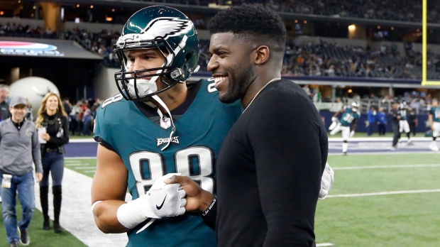 In this Nov. 19, 2017, file photo, then-Philadelphia Eagles tight end Trey Burton (88) has a photo taken with former Eagles linebacker Emmanuel Acho prior to an NFL football game against the Dallas Cowboys in Arlington, Texas. Acho has enjoyed a spectacular rise off the field, beginning with his desire to take on racism. (AP Photo/Michael Ainsworth)