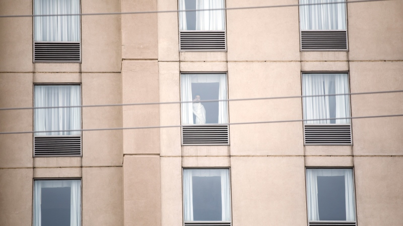 A guest is seen in a hotel window in Mississauga, Ont. by the Pearson International Airport on Monday, Feb. 22, 2021 as new air travel rules come into effect in Canada. THE CANADIAN PRESS/Cole Burston