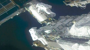 In this image taken from NASA video, NASA astronauts Kate Rubins, top, and Victor Glover work outside the International Space Station Sunday, Feb. 28, 2021. The