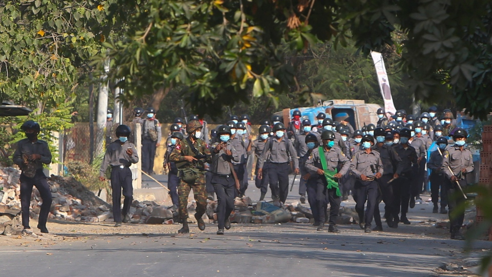 Myanmar riot police crossing blockage during a protest against the military coup in Mandalay, Myanmar, Sunday, Feb. 28, 2021. Security forces in Myanmar used lethal force as they intensified their efforts to break up protests a month after the military staged a coup. At least four people were reportedly killed on Sunday. (AP Photo)