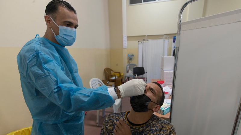 A health care worker takes a nasal swab sample from a Palestinian man at a COVID-19 testing center, in the West Bank city of Ramallah, Thursday, Feb. 25, 2021. (AP Photo/Nasser Nasser)