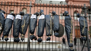 Demonstrators hung mock body bags in front of the Casa Rosada presidential office in Buenos Aires to protest against a scandal over vaccine line-jumping. (AFP)