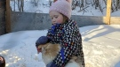 Lennon, 4, took a chicken along for a short ride on a saucer down a snowpile near Grandora. Photo by Tenille Poole
