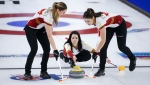Team Canada skip Kerri Einarson makes a shot against Team Alberta as second Shannon Birchard, right, and lead Briane Meilleur sweep in the semi-final at the Scotties Tournament of Hearts in Calgary, Alta., Sunday, Feb. 28, 2021.THE CANADIAN PRESS/Jeff McIntosh