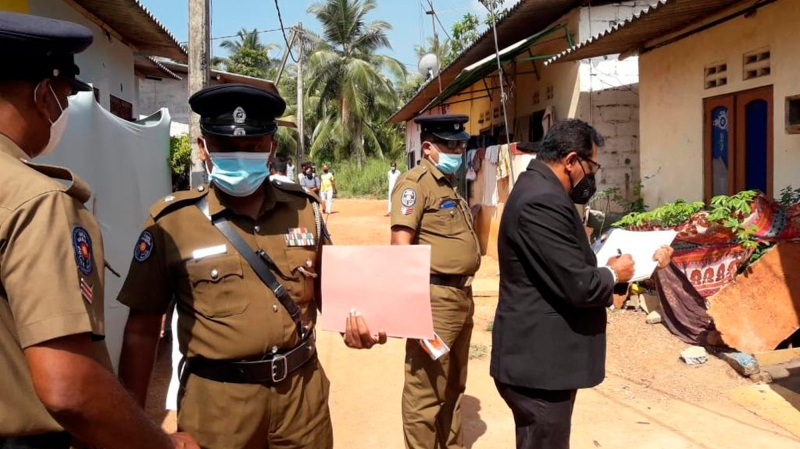 Sri Lankan magistrate Wasantha Ramanayake, right and police officers inspect outside a house where a nine year old girl was canned to death in Delgoda, Sri Lanka, Sunday, Feb. 28, 2021. (AP Photo/Sudath Pubudu Keerthi)