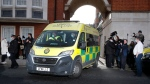 Police officers stand at an entrance to the King Edward VII Hospital in London where Prince Philip is being treated for an infection, as an ambulance is driven out, on March 1, 2021. (Frank Augstein / AP)