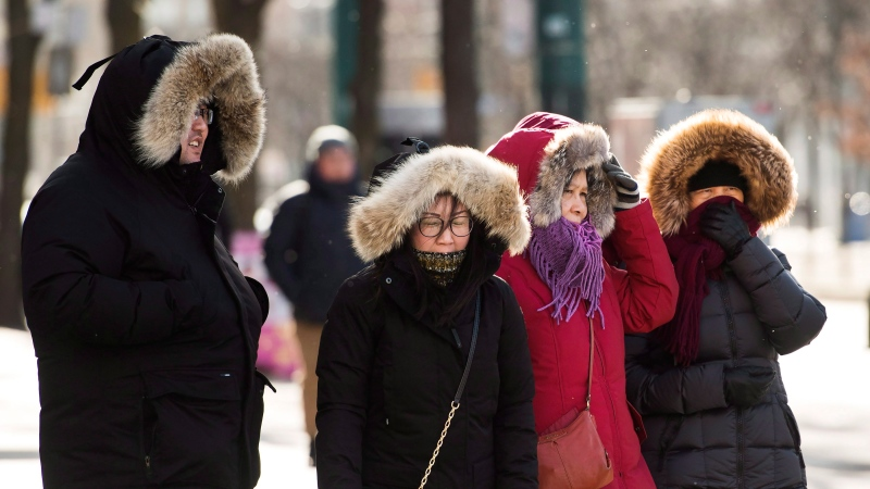 People wait to cross a street in Chinatown during a cold and windy day in Toronto on Thursday, January 10, 2019. THE CANADIAN PRESS/Nathan Denette