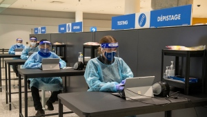 Workers prepare to greet passengers at the COVID-19 testing centre in the International Arrivals area at Pearson Airport in Toronto on Tuesday January 26, 2021. THE CANADIAN PRESS/Frank Gunn