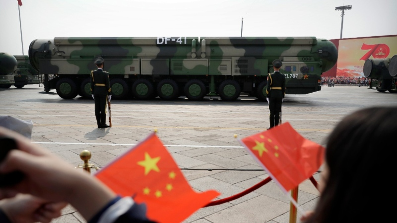 FILE - In this Oct. 1, 2019, file photo spectators wave Chinese flags as military vehicles carrying DF-41 ballistic missiles roll during a parade to commemorate the 70th anniversary of the founding of Communist China in Beijing. (Mark Schiefelbein / AP)