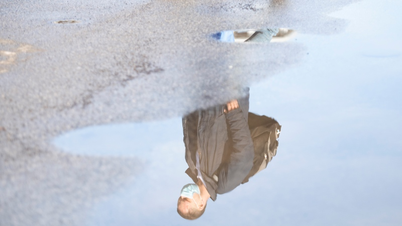 A man wears a face mask as he is reflected in a pool of water in Montreal, Sunday, February 28, 2021, as the COVID-19 pandemic continues in Canada and around the world. THE CANADIAN PRESS/Graham Hughes