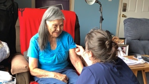 An Ahousaht First Nation member with a public health worker during the community's COVID-19 vaccination program. (Greg Louie)