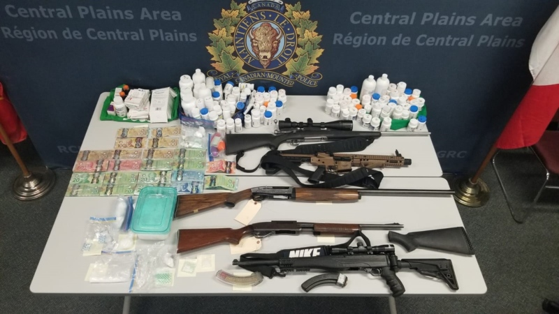 A supplied photo of the guns, drugs and money seized by police.