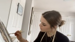 Laura Kelly in her home studio working on some of her art. (Dave Charbonneau / CTV News Ottawa)