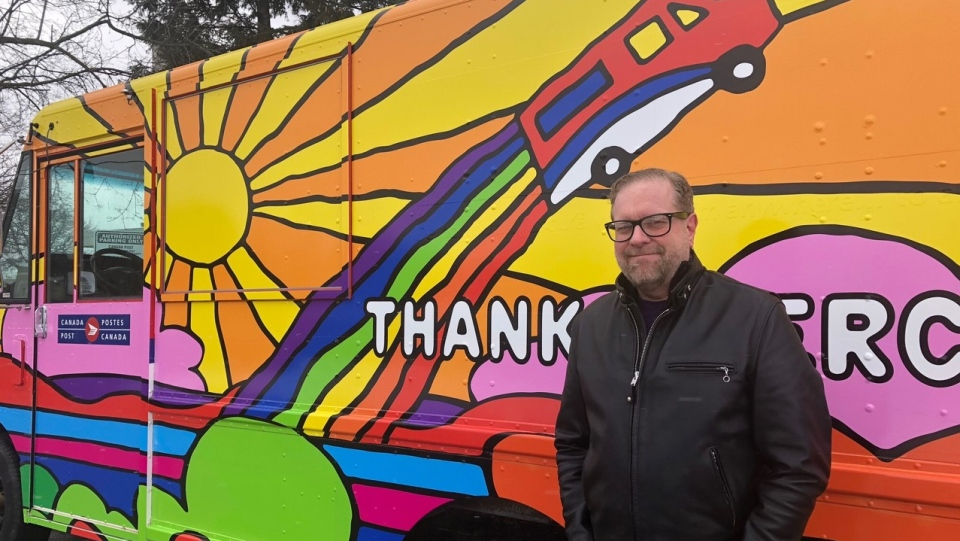 Graphic artist Andrew Lewis stands in front of a Canada Post truck covered in his work in London, Ont. on Monday, March 1, 2021. (Jordyn Read / CTV News)