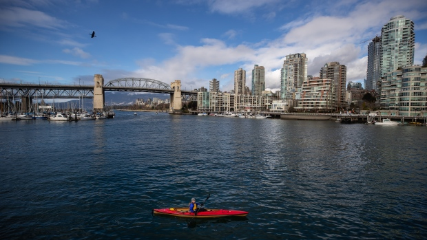 A man paddles a kayak on False Creek as the Burrard Bridge and condo towers are seen in the distance, in Vancouver, on Tuesday, Feb. 16, 2021. (Darryl Dyck / THE CANADIAN PRESS)