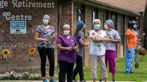Workers hold flowers given to them as they watch as 150 nursing union members show support at Orchard Villa Long-Term Care in Pickering, Ontario on Monday June 1, 2020. THE CANADIAN PRESS/Frank Gunn