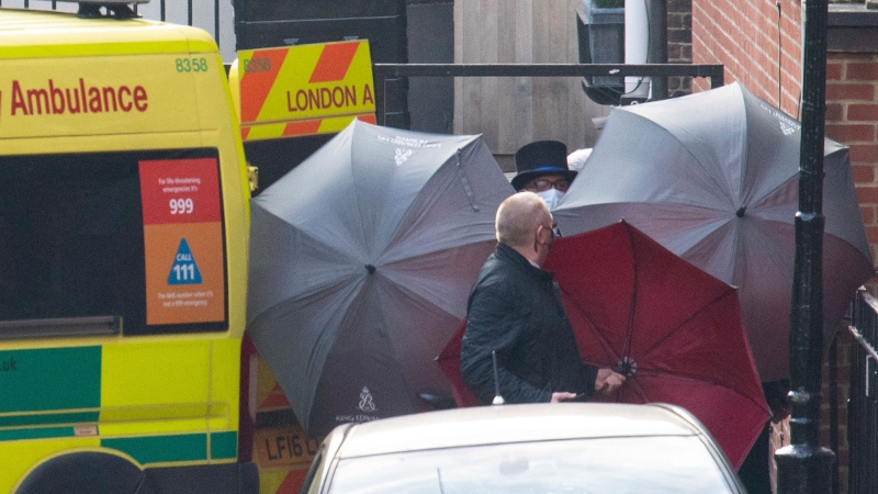 Staff shield the exit with umbrellas alongside an ambulance outside the rear of the King Edward VII Hospital in London, Monday March 1, 2021. Buckingham Palace said Monday March 1, 2021, that Prince Philip has been transferred from King Edward VII's Hospital to St Bartholomew's Hospital in London to continue his treatment. (Dominic Lipinski/PA via AP)