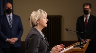 Dr. Bonnie Henry speaks as Premier John Horgan and Minister Arian Dix look on during a news conference at Legislature in Victoria on Monday, March 1, 2021. (Chad Hipolito / THE CANADIAN PRESS)