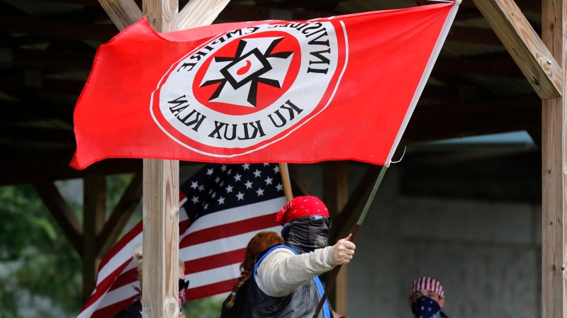 """In this Sept. 1, 2018 photo, a Ku Klux Klan member waves a Klan flag during the Ku Klux Kookout where counter protests by anti-hate groups were also held at Jaycee Park in Madison, Ind. The event was organized by a chapter of the KKK, who call themselves the Honorable Sacred Knights. Madison Mayor Damon Welch is distancing his community from the group who are planning a rally in Ohio this month. Welch said Wednesday, May 15, 2019, the city doesn't """"stand for any type of hate"""" and doesn't support the group's views. (Michelle Pemberton/The Indianapolis Star via AP)"""