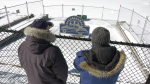 Don DeGroot (left) and Dave Sheridan (right) look over the Old Meg ii statue sitting on the ice along Blockhouse Island in Brockville, Ont. (Nate Vandermeer / CTV News Ottawa)