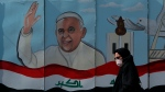 A woman walks past a mural depicting Pope Francis on a concrete wall placed by Iraqi security forces to surround the Our Lady of Salvation Church during preparations for the Pope's visit in Baghdad, Iraq, Monday, March 1, 2021. (AP/Photo/Khalid Mohammed)