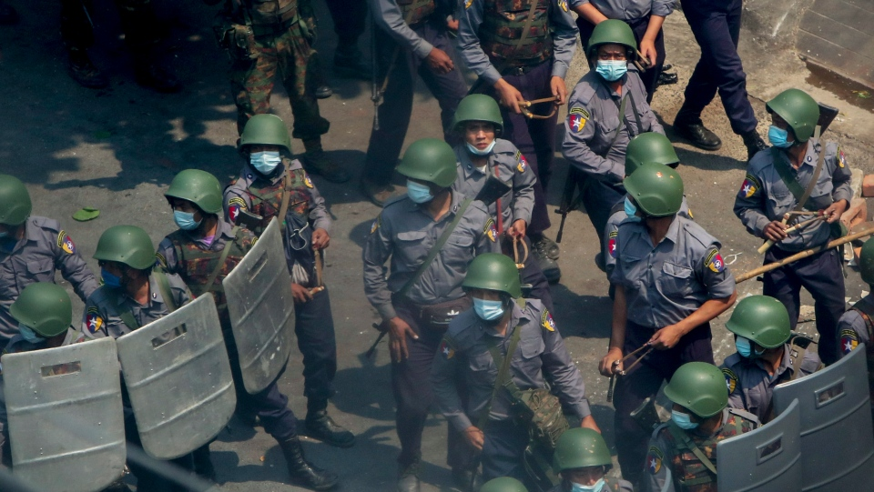 Policemen and soldiers armed with guns and slingshots advance towards anti-coup protesters in Mandalay, Myanmar, Wednesday, March 3, 2021. (AP Photo)