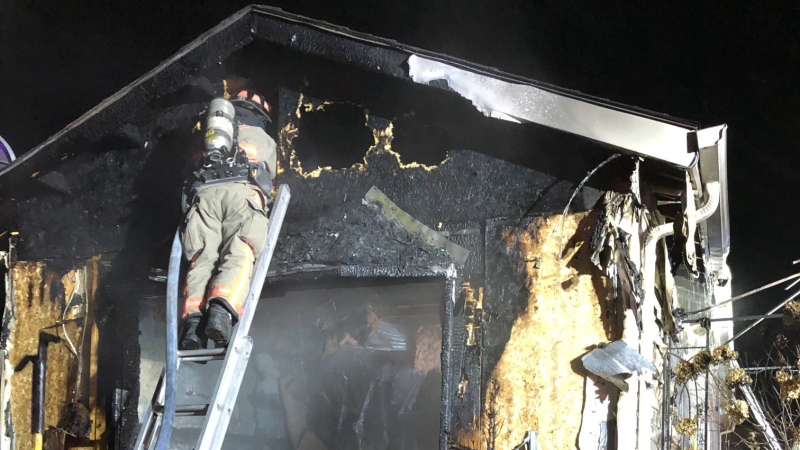 A firefighter battles hot spots in a house fire in Essex on Tuesday, March. 3, 2021. (Essex Fire and Rescue)