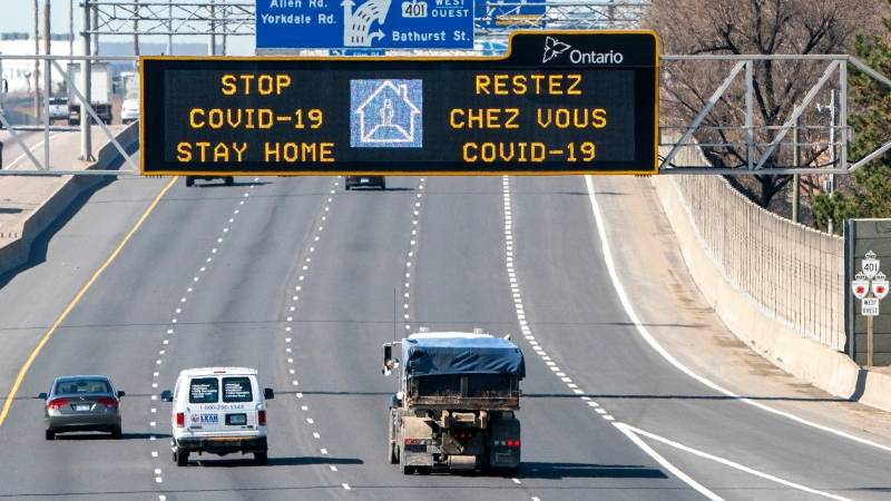 Traffic on Highway 401 in Toronto passes under a COVID-19 sign on Monday April 6, 2020. (THE CANADIAN PRESS / Frank Gunn)