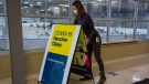 A person stands up a sign for COVID-19 vaccine at the Invista Centre in Kingston, Ont., on Monday Mar. 1, 2021. The centre will be used as a COVID-19 vaccination site for the KLF&A area. (Lars Hagberg/THE CANADIAN PRESS)