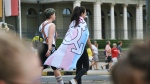 File photo of person with a trans flag on their back. (Unsplash, Delia Giandeini)
