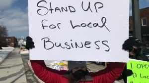 A protester holds a sign to support local businesses in Midland, Ont. on Wed. March 3, 2021 (Rob Cooper/CTV News)
