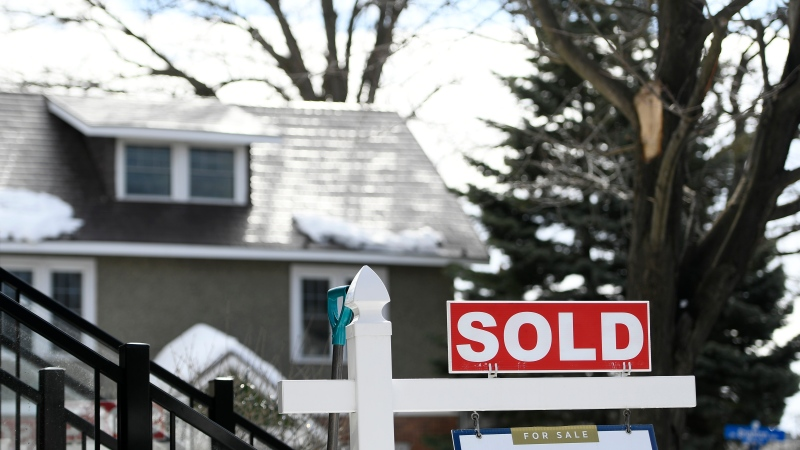A for sale sign outside a home indicates that it has been sold, in Ottawa, on Monday, March 1, 2021. (Justin Tang/THE CANADIAN PRESS)
