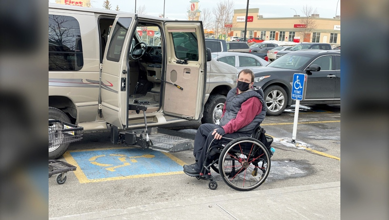 Erik Freiburger beside his accessible van that he has to park at an angle to ensure he and his wife can get in and out when they need to rather than blocked in by another vehicle