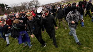 FILE - In this Wednesday, Jan. 6, 2021 file photo Ethan Nordean, with backward baseball hat and bullhorn, leads members of the far-right group Proud Boys in marching before the riot at the U.S. Capitol. Nordean, 30, of Auburn, Washington, has described himself as the sergeant-at-arms of the Seattle chapter of the Proud Boys. The Justice Department has charged him in U.S. District Court in Washington, D.C., with obstructing an official proceeding, aiding and abetting others who damaged federal property, and knowingly entering or remaining in a restricted building. (AP Photo/Carolyn Kaster,File)