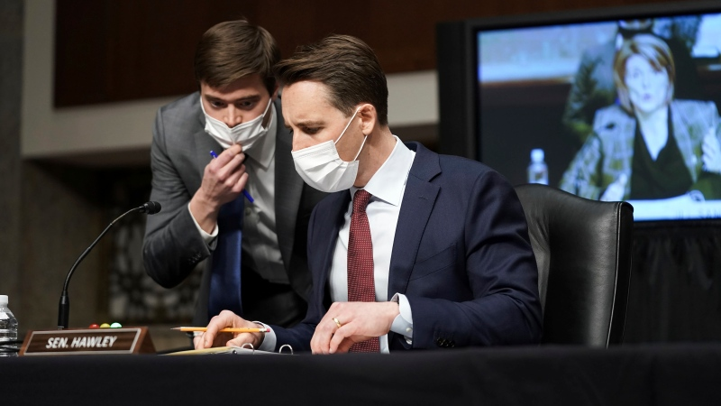 Sen. Josh Hawley, R-Mo., speaks to an aide during a Senate Committee on Homeland Security and Governmental Affairs and Senate Committee on Rules and Administration joint hearing Wednesday, March 3, 2021, examining the January 6, attack on the U.S. Capitol in Washington. (Greg Nash/Pool via AP)