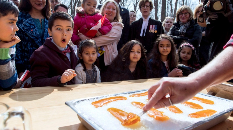 New Canadian citizen David Alfonso, 8, reacts as he watches maple taffy being rolled for him and other new Canadians after a citizenship ceremony in this file photo dated Wednesday, April 11, 2018. THE CANADIAN PRESS/Justin Tang