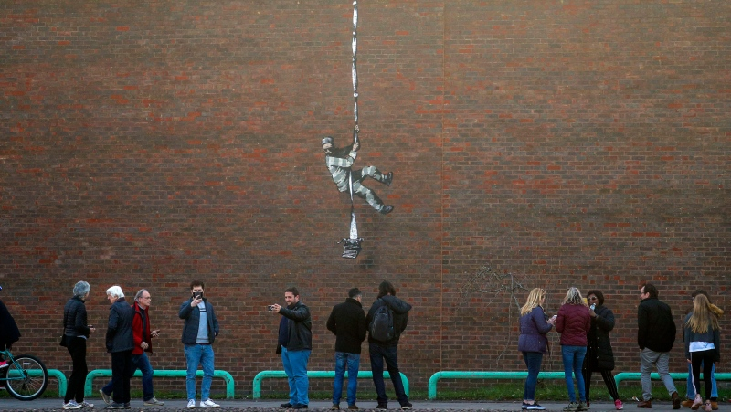 Banksy's latest artwork which appeared in Reading, England, March 1, 2021. Street artist Banksy has confirmed that he was behind the artwork that appeared on the red brick wall of a former prison in the English town of Reading. The elusive artist confirmed the picture was his on Thursday March 4, 2021, when he posted a video on his Instagram account. (Steve Parsons/PA via AP)