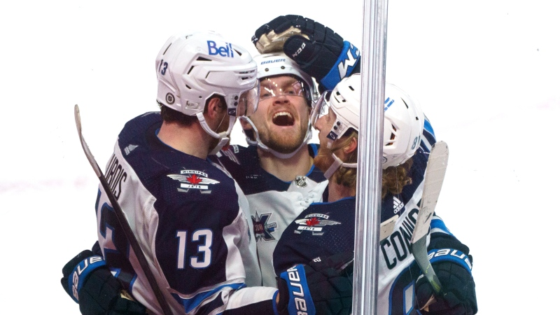 Winnipeg Jets' Pierre-Luc Dubois, left, celebrates his game winning goal with teammates Nikolaj Ehlers, centre, and Kyle Connor to defeat the Montreal Canadiens during overtime NHL hockey action in Montreal on Thursday, March 4, 2021. THE CANADIAN PRESS/Paul Chiasson