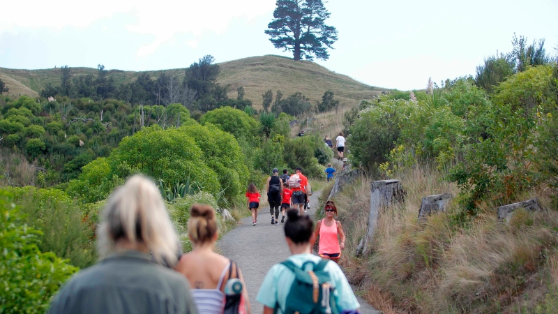 People walk up a hill above Papamoa Beach, New Zealand, as a tsunami warning is issued Friday, March 5, 2021. (George Novak/New Zealand Herald via AP)