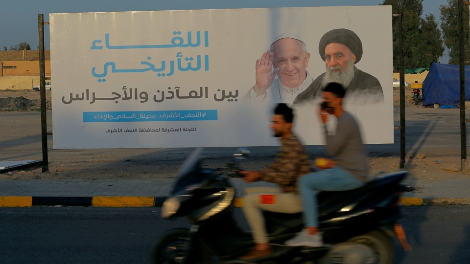 Iraqis put up a poster announcing the upcoming visit of the Pope Francis and a meeting with a revered Shiite Muslim leader, Grand Ayatollah Ali al-Sistani, right, in Najaf, Iraq, Thursday, March 4, 2021. (AP Photo/Anmar Khalil)