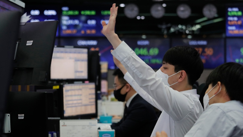 A currency trader gestures at the foreign exchange dealing room of the KEB Hana Bank headquarters in Seoul, South Korea, Thursday, March 4, 2021. (AP Photo/Ahn Young-joon)