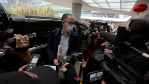 Peter Ben Embarek of a World Health Organization team speaks to journalists as he arrives at the VIP terminal of the airport to leave, at the end of their WHO mission to investigate the origins of the coronavirus pandemic in Wuhan in central China's Hubei province Wednesday, Feb. 10, 2021. (AP Photo/Ng Han Guan)