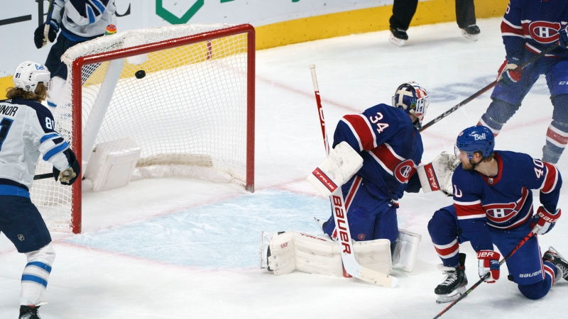 The puck goes into the net past Montreal Canadiens goaltender Jake Allen on a goal by Winnipeg Jets' Pierre-Luc Dubois (not shown) as Canadiens' Joel Armia looks on during overtime in NHL hockey action in Montreal on Thursday, March 4, 2021. THE CANADIAN PRESS/Paul Chiasson