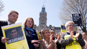 Ensaf Haider, centre right, wife of Raif Badawi, applauds during a vigil for her husband still in prison in Saudi Arabia, Thursday, May 7, 2015 at the legislature in Quebec City. MNA Luc Fortin, from the left, Quebec's International Relations Minister Christine St-Pierre, Ensaf Haider and Opposition legislature Leader Agnes Maltais look on. THE CANADIAN PRESS/Jacques Boissinot