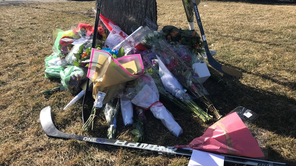 Flowers, messages, and hockey sticks lay under a tree at the Gretzky family home (Dan Lauckner / CTV News Kitchener)