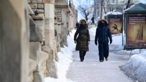 A couple of people make their way along Wellington Street in Ottawa Friday, March 5, 2021. (Sean Kilpatrick/THE CANADIAN PRESS)