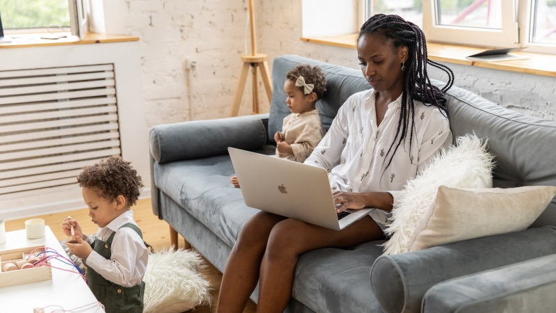 A mother is seen working from home with her two kids. (Ekaterina Bolovtsova/Pexels)