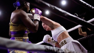Claressa Shields, left, tries to avoid a left from Marie-Eve Dicaire during the seventh round of a boxing bout for the women's super welterweight title Friday, March 5, 2021, in Flint, Mich. (AP Photo/Carlos Osorio)